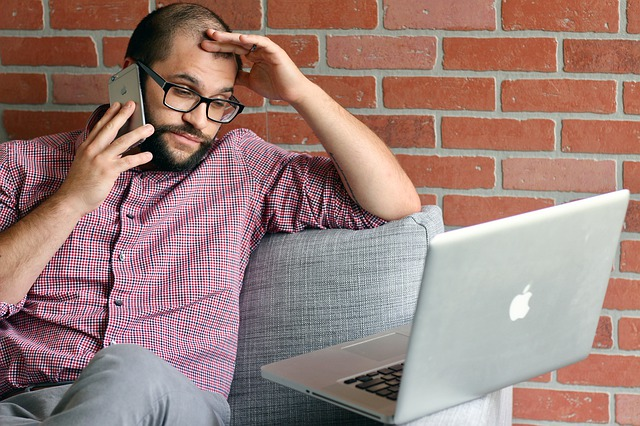 man talking on the phone while working on their laptop